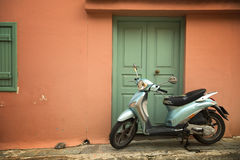 Blå sparkcykel på en persikavägg Royaltyfri Fotografi