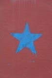 Blå stjärna på den burgundy väggen Ett begreppsfotografi Fotografering för Bildbyråer