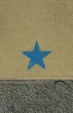 Blå stjärna på den smutsiga ockran och grå färgväggen Ett begreppsfotografi Arkivbilder