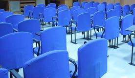 Blå stol i ett konferensrum Arkivfoto