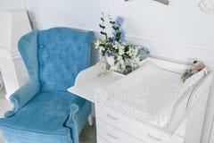 Blå stol och ändrande tabell för spädbarn inre av ett rymligt rum för barn` s Royaltyfri Bild