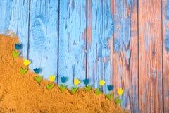 Blå tappningbakgrund med blommor i sand royaltyfria foton