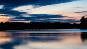 Blå timmeblick på ö sjön och gåbron Arkivbilder