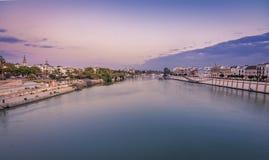 Blå timmevew av seville och torre del oro från trianabron fotografering för bildbyråer