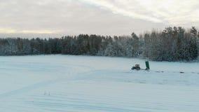 Blå traktor med den lyftta släpkroppen, som gödslar jorden med dolomitemjöl i vintern för att öka avkastningen arkivfilmer
