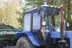 Blå traktor med släpet Fotografering för Bildbyråer