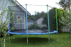 Blå trampolin på gräsmattan i trädgård Fotografering för Bildbyråer