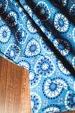 Blå tygtextil med prydnaden på trä Royaltyfri Foto