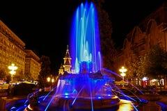 Blå upplyst springbrunn på Plazaoperan i Timisoara Arkivfoton