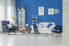 Blå vardagsrum med soffan arkivfoto
