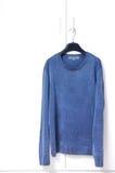 Blå varm tröjahängning på den vita hemliga dörren Fotografering för Bildbyråer