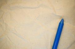 blå vaxfärgpenna på en återanvänd skrynklig pappers- yttersida Royaltyfri Bild