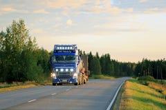 Blå Volvo FH lastbil på vägen på Dusktime Fotografering för Bildbyråer