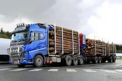 Blå Volvo FH16 700 timmerlastbil med journalsläpet Arkivfoton