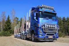 Blå Volvo FH16 750 timmerlastbil på den lantliga vägen Arkivbilder