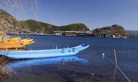 Blå wood fiskebåt som svävar på Lugu för blått vatten som den sceniska fläcken för sjö omges av snöberget och hög himmel Arkivbild
