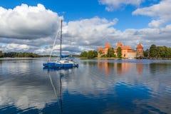 Blå yacht på Galve sjön, Litauen med den Trakai slotten på backgr Arkivfoton