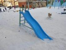 Blåa barns glidbana i snön parkerar område av ‹för †staden Royaltyfria Bilder