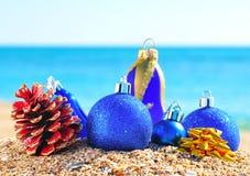Blåa baubles för jul, kottar på sanden Royaltyfri Foto