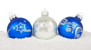 Blåa baubles för jul på snow Arkivfoto