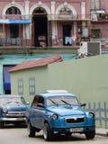 BLÅA BILAR, BALKONG MED JÄRNRÄCKE OCH TVÄTTERI, HAVANNACIGARR, KUBA Royaltyfri Fotografi