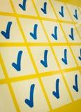Blåa checkmarks i gult raster Arkivbild