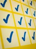 Blåa checkmarks i gult raster Royaltyfri Fotografi
