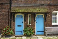 Blåa dörrar och mossa täckte tegelplattor, London, England Royaltyfri Bild