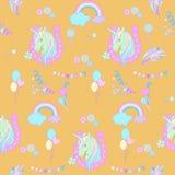 Blåa enhörningar i rosa hästsko på en gul bakgrund med ballonger och regnbågar Arkivfoton