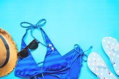 Blåa färgbikini, solglasögon, hatt och pricksandaler på blå bakgrund, lekmanna- sommar för lägenhet Arkivfoton