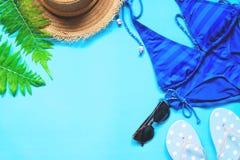 Blåa färgbikini, solglasögon, hatt och pricksandaler på blå bakgrund, lekmanna- sommar för lägenhet Fotografering för Bildbyråer