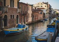 Blåa fartyg på den Venetian kanalen royaltyfri bild