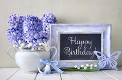 Blåa garneringar och hyacintblommor på den vita tabellen, svart tavla Royaltyfria Bilder