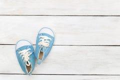 Blåa gymnastikskor för lite pojke på en vit träbakgrund Moc Royaltyfria Bilder