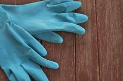 Blåa handskar för trädgårds- arbete på det wood golvet Arkivbild
