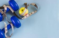 Blåa hantlar och att mäta bandet och äpplet på en blå bakgrund arkivbild
