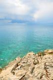 Blåa hav och moln med ojämna klippor royaltyfria bilder