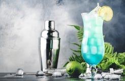 Blåa Hawaii eller blå lagun - alkoholiserad coctail för sommar med vodka, likör, uppiggningsmedel, ananasfruktsaft och is, i hög  arkivfoton