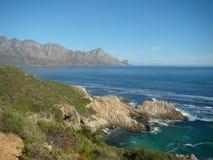 Blåa himlar för berg och kust- vatten royaltyfri bild