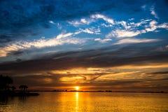 Blåa himlar och guld- solnedgång på havsaftonseascape Arkivfoto