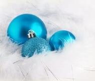 Blåa julbaubles på slappa vita fjädrar Fotografering för Bildbyråer