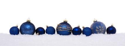 Blåa julbollar som isoleras på snö arkivfoton