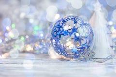 Blåa julexponeringsglasboll och prydnader på ljus silverferie fotografering för bildbyråer