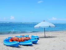 Blåa kajaker, orange livjakets och vitt strandparaply Royaltyfri Foto