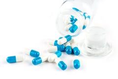 Blåa kapslar med den genomskinliga flaskan, sjukvård och medicin Arkivfoto