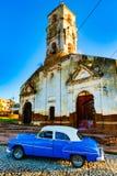 Blåa klassiska Chevy parkeras framme av abaondoned kyrka Royaltyfria Bilder