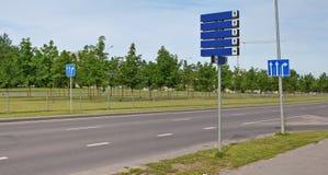 Blåa ljusa reflekterande vägmärken med vita pilar Arkivbild