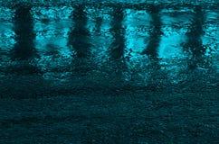 Blåa ljusa reflexioner på en våt väg Royaltyfri Bild