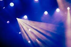 Blåa ljusa strålar från strålkastaren till och med röken på teatern eller konserthallen Belysningsutrustning för en kapacitet ell royaltyfri fotografi