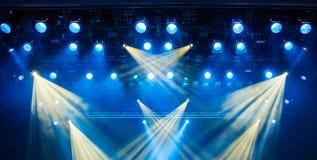 Blåa ljusa strålar från strålkastaren till och med röken på teatern eller konserthallen Belysningsutrustning för en kapacitet ell arkivbilder